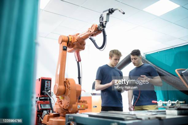 two male engineers controlling robotic welder in factory. - engineer stock pictures, royalty-free photos & images