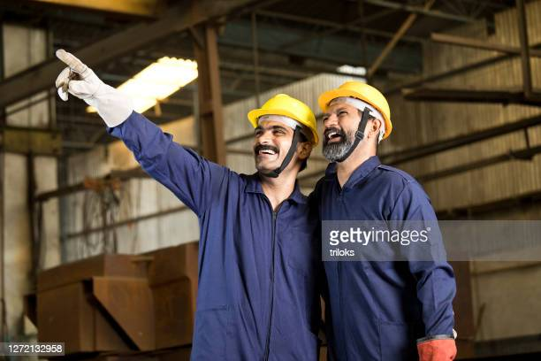two male engineers looking away at factory - uniform stock pictures, royalty-free photos & images