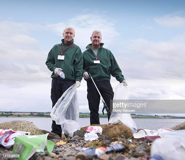 two male environmentalists removing litter from seashore - working seniors stock pictures, royalty-free photos & images