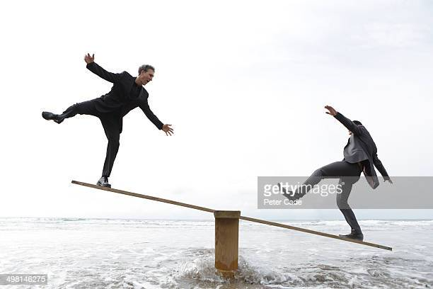 two male executives balancing on seesaw - standing on one leg stock pictures, royalty-free photos & images