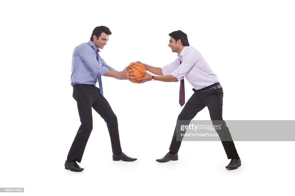 Two male executives holding a basketball : Stock Photo