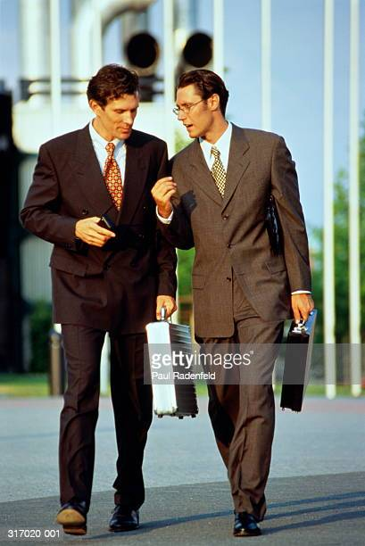 Two male executives in conversation,walking outdoors