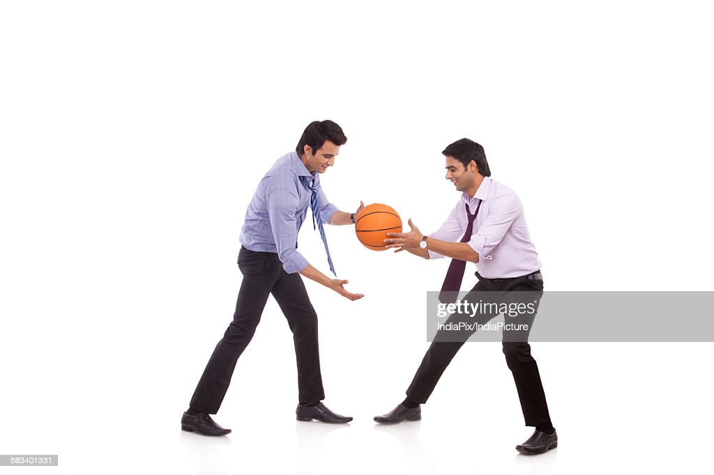 Two male executives playing basketball : Stock Photo