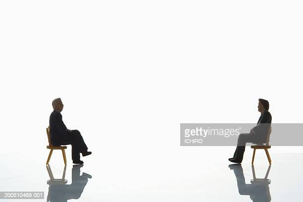 Two male figurines sitting on chairs, facing one another, side view