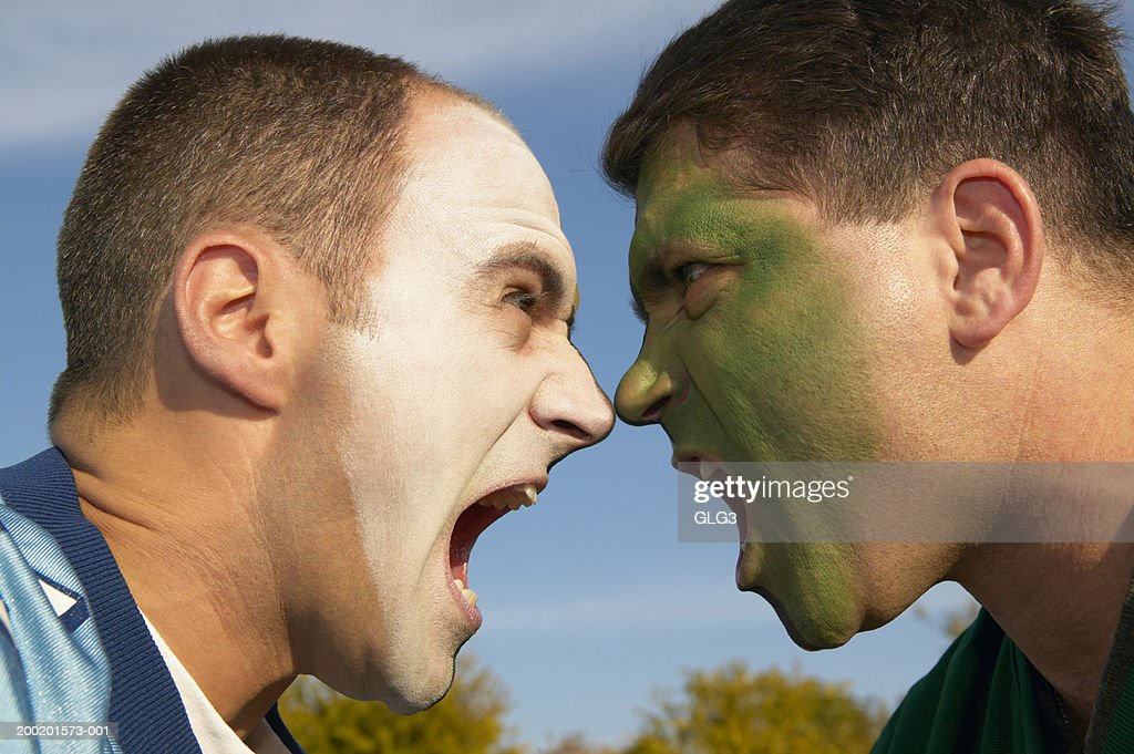 two male football fans in face paint shouting side view closeup