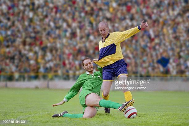 two male footballer players in tackle on pitch - tackling stock pictures, royalty-free photos & images