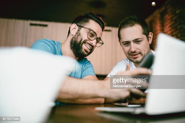 Two Male Freelancers Drinking Coffee and Working In Coffee Restaurant
