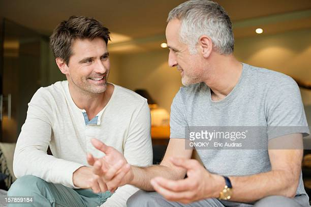 Two male friends discussing and smiling
