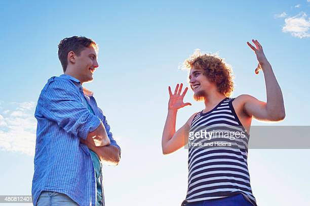 Two male friends enjoying conversation in sunlight
