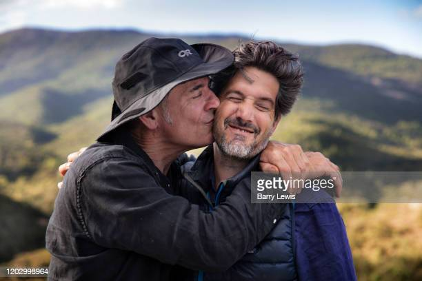Two male friends having a joking embrace and kiss in the Frence countryside 5th October 2019 near the village of Terme, France. In France the kiss or...