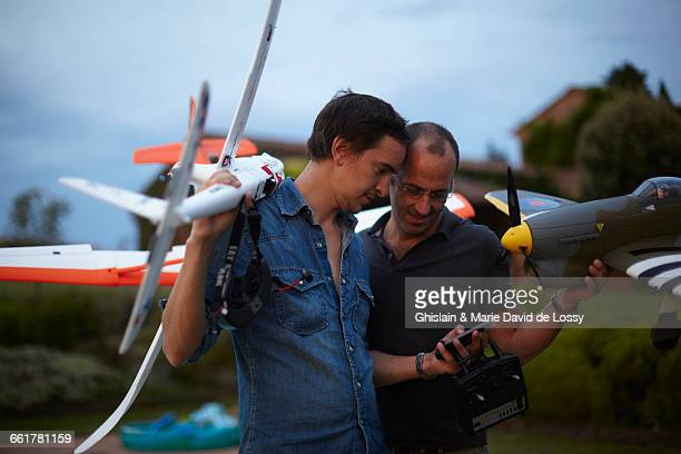 Two male friends holding remote control planes, looking at smartphone