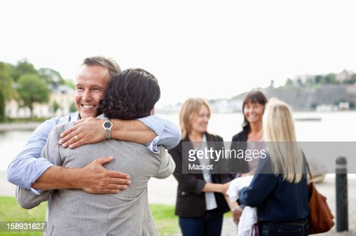 Two Male Friends Hugging Each Other With Female Colleagues In Background High-Res -5740