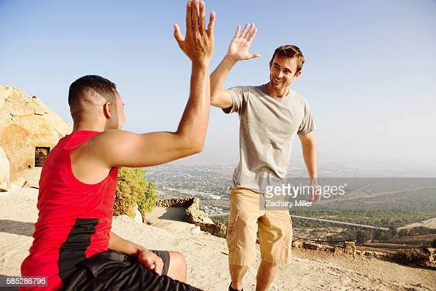 Two male friends, on top of mountain, giving high five