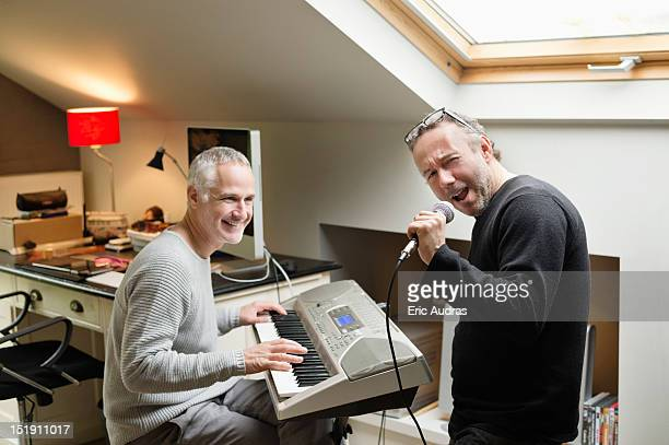 two male friends playing a piano and singing - electric piano stock photos and pictures