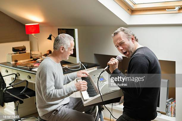 two male friends playing a piano and singing - keyboard player stock photos and pictures
