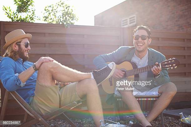 Two male friends playing guitar at rooftop party