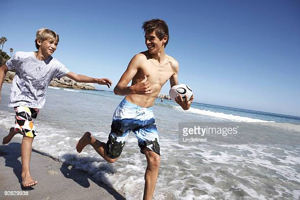 Two male friends playing rugby on the beach