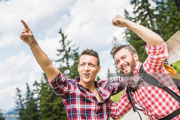 Two male friends pointing and cheering