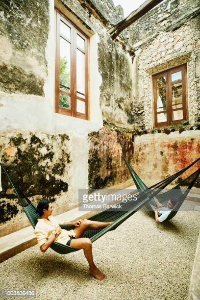 Two male friends relaxing in hammocks at luxury resort