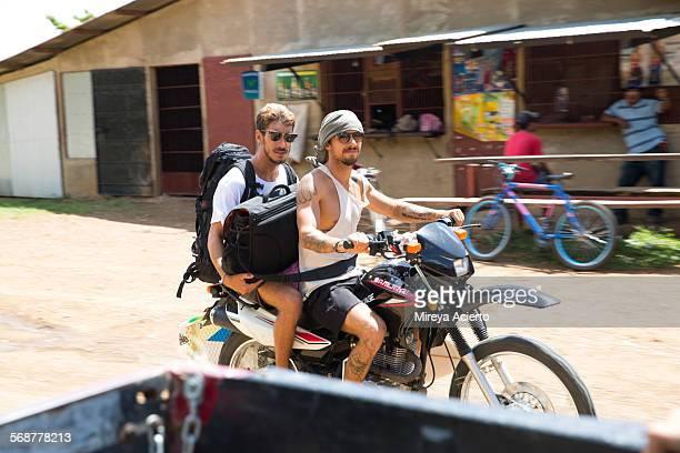 Two male friends ride a mortorcylce