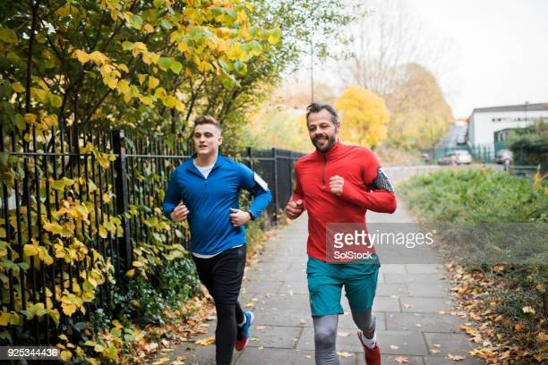 two male friends running together - organised group stock pictures, royalty-free photos & images