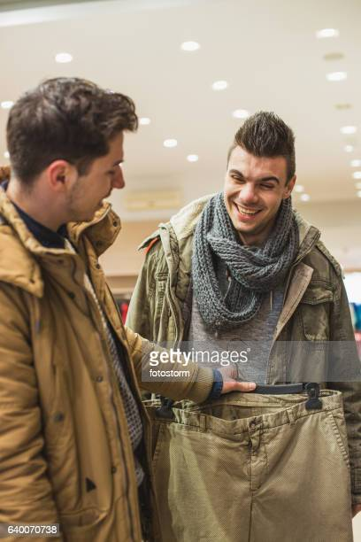 Two male friends shopping for pants