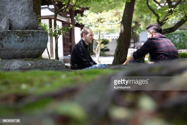 Zwei männliche Freunde sitzen im Tempel