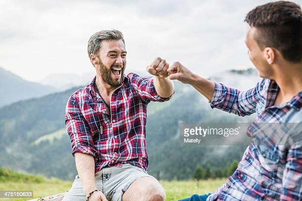 two male friends sitting on fence, tyrol austria - männerfreundschaft stock-fotos und bilder