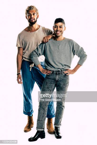 two male friends standing together on white background - nosotroscollection stockfoto's en -beelden