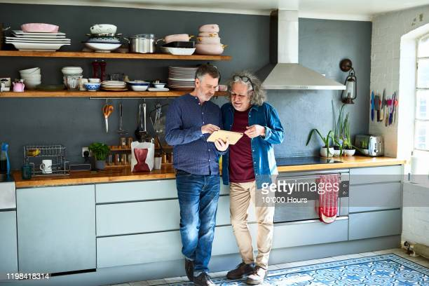 two male friends using digital tablet together in kitchen - planning stock pictures, royalty-free photos & images