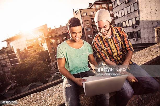 Two male friends working on laptop