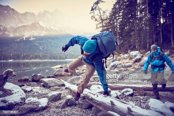 Two male hikers jumping logs by snowy Lake Eibsee, Zugspitze, Bavaria, Germany
