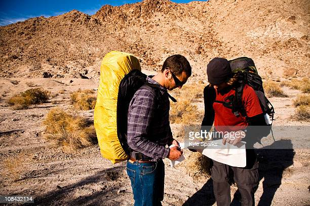 Two male hikers look over a map while backpacking through the Confidence Hills in Death Valley Nation Park, California.