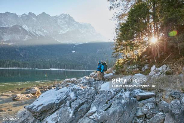 Two male hikers looking out from rocks at Lake Eibsee in winter, Zugspitze, Bavaria, Germany