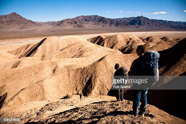 Two male hikers search to find the best route through Death Valley's Confidence Hills, in California, while on backing packing.
