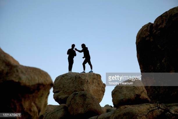 two male hikers silhouetted against a blue sky, atop a boulder in joshua tree national park - timothy hearsum stockfoto's en -beelden