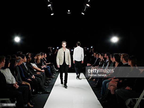 Two male models walking on catwalk