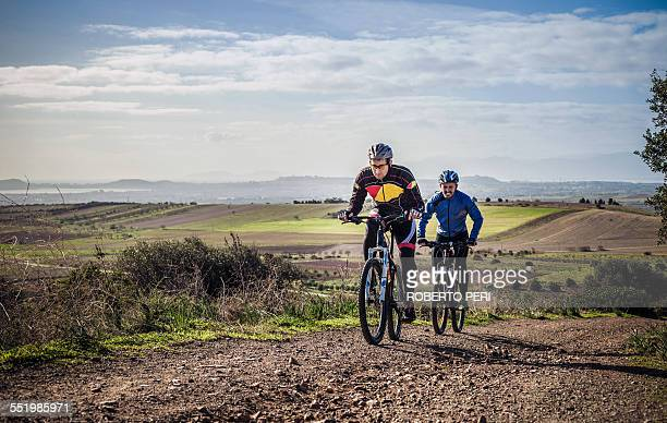 Two male mountain bikers cycling up dirt track, Cagliari, Sardinia, Italy