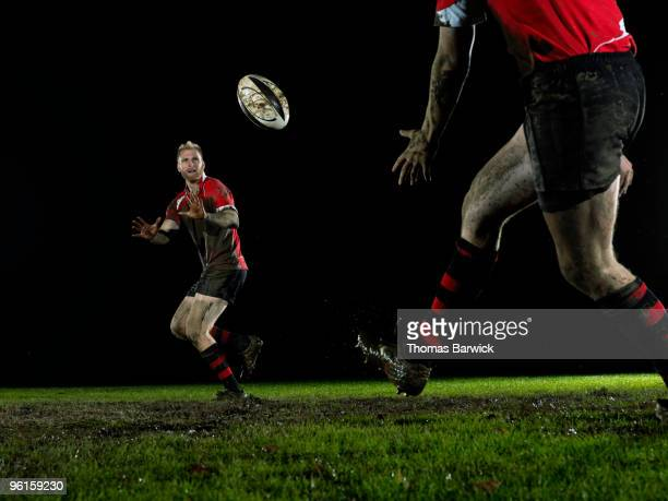 two male rugby players passing ball on field - passing sport stockfoto's en -beelden