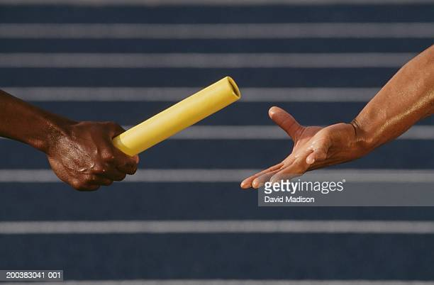 two male runners passing relay baton, side view, close-up of hands - ball passen stock-fotos und bilder