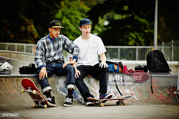 Two male skaters watching friends skate in park