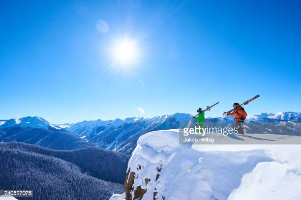 two male skiers looking out from snow covered ridge, aspen, colorado, usa - aspen colorado stock pictures, royalty-free photos & images