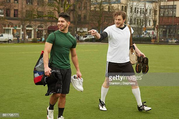Two male soccer players carrying gym bags on soccer pitch