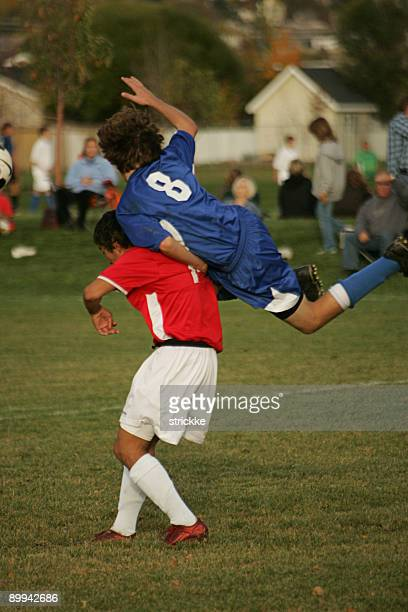 Two Male Soccer Players Collide in Midair Vying for Header