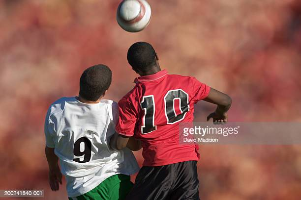 Two male soccer players competing for ball (Digital Composite)