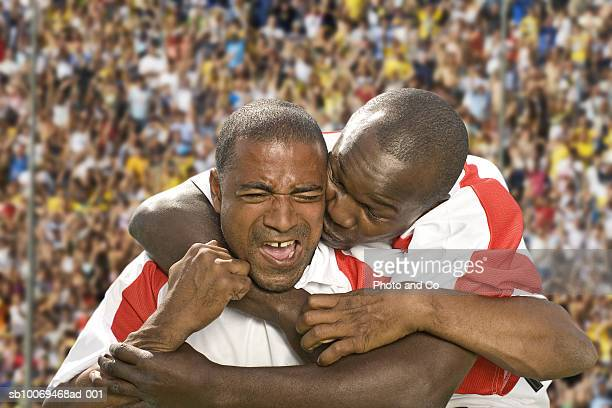 Two male soccer players embracing in stadium