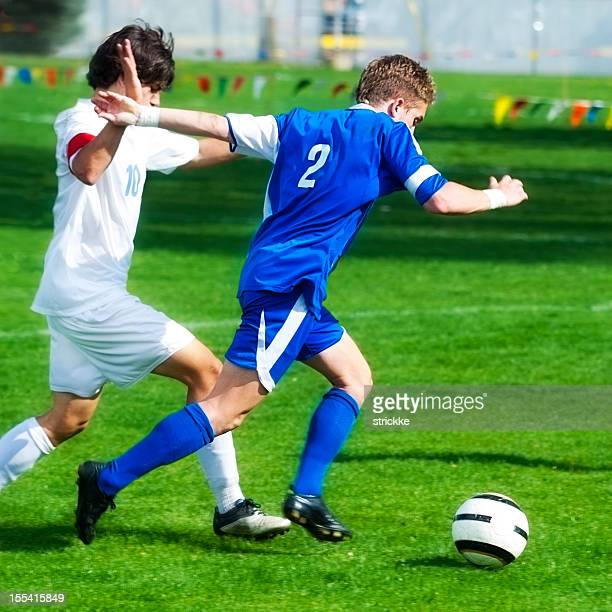 Two Male Soccer Players Engage in Hand Battle for Ball