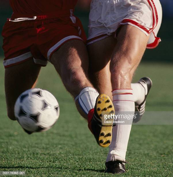 Two male soccer players fighting for ball  (Digital Enhancement)