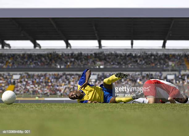 two male soccer players lying down after tackle in stadium - tackling stockfoto's en -beelden