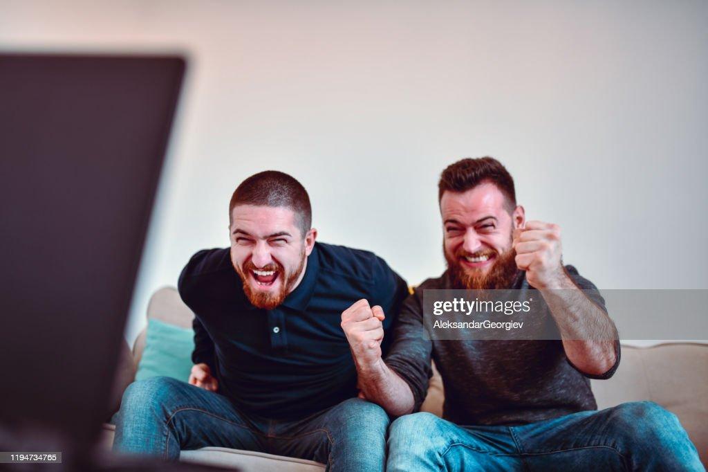 Två manliga sportfantaster njuter spänd fotbolls match : Bildbanksbilder